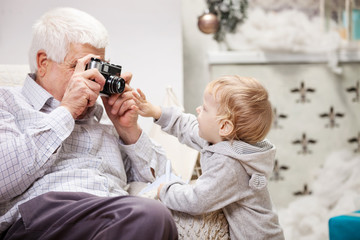 Senior man taking photo of his grandson at Christmas time