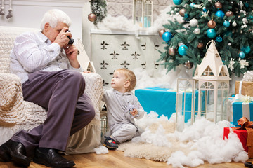 Senior man taking photo of toddler grandson near Christmas tree