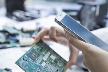 Women who have the electronic parts and mobile phone