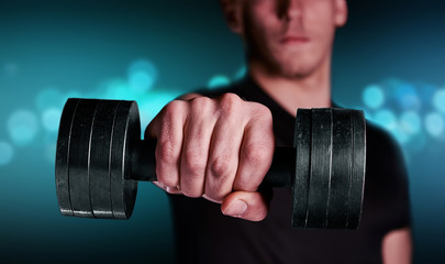 Fitness man with dumbbell, focus on dumbbell