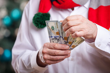 Man in bright scarf holding one hundred dollar banknotes