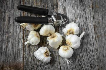 Garlic Bulbs with Garlic Press on Rustic Wood Background