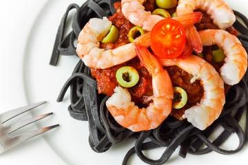 Black pasta with tomato sauce and shrimp, closeup