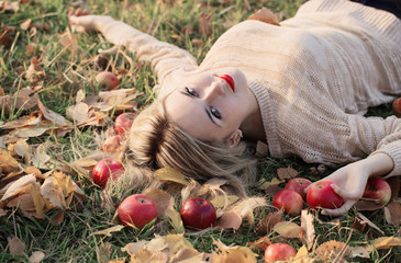 Girl with the apple is lying on the grass