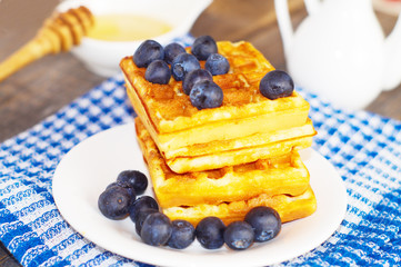Belgian waffles with blueberries on the wooden rustic surface