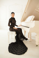 Beautiful girl in a long black dress at the piano.