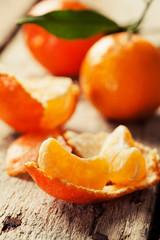 Open tangerine on wooden background