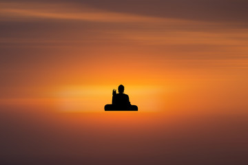 silhouette of buddha and sunset background with blur motion
