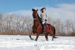 Young woman horseback riding on a snowy glade
