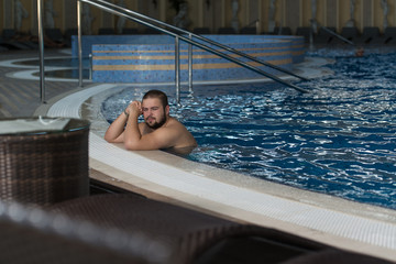 Overweight Man Relaxing In The Swimming Pool