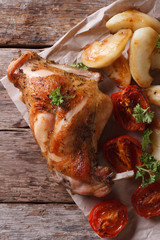 roasted rabbit leg with apples and tomatoes top view vertical