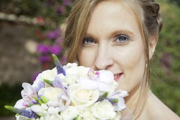 Primer plano de novia con ojos azules y ramo de flores