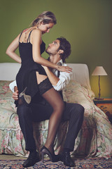 Handsome elegant man undressing woman