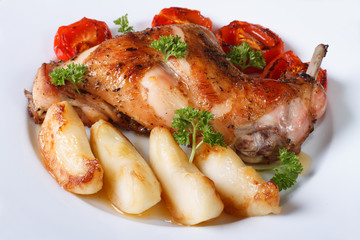 Rabbit leg roasted with apples and tomatoes on a plate close-up