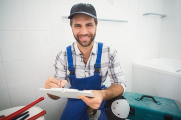 Plumber taking notes on clipboard