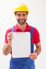 Construction worker showing clipboard to camera