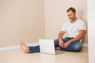 Happy man using laptop after moving in