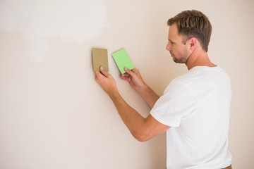 Handsome decorator sanding down the wall