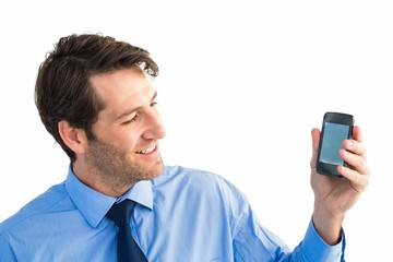 Smiling businessman showing smartphone to camera