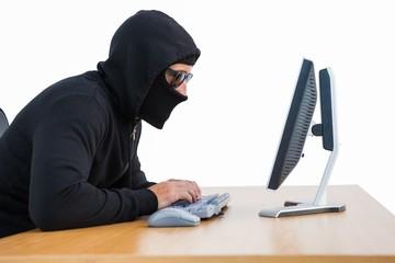 Burglar with sunglasses typing on keyboard