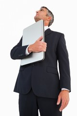 Businessman in suit holding his laptop proudly