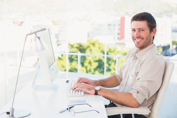 Smiling businessman using his computer at his desk