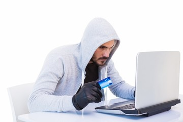 Burglar doing online shopping with laptop and credit card