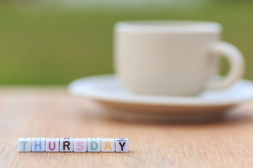 Thursday written in letter beads and a coffee cup on table