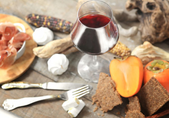 red wine glass with winter laid table in the background