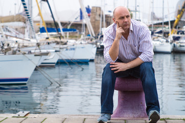 Businessman sitting by expensive sailing boats and yachts in a c