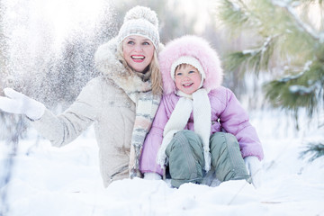 Happy family mother and daughter sitting in snow outdoor