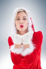 Festive blonde blowing a kiss