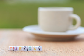Tuesday written in letter beads and a coffee cup on table