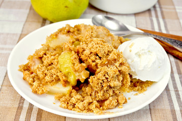 Crumble with pears in plate on tablecloth