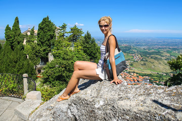 Attractive girl sitting on a stone in the fortress of San Marino