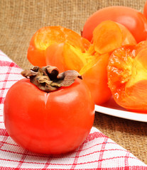 Ripe persimmon fruits on white plate and napking,  sacking backg