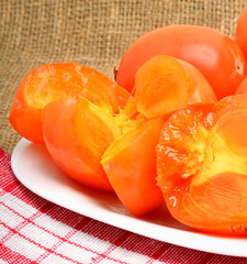 Ripe persimmon fruits on white plate and napking, sacking backgr
