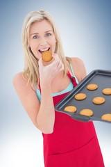Happy blonde eating hot cookies