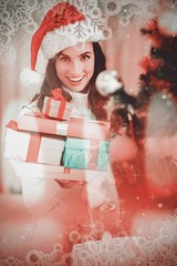 Brunette holding pile of gifts near a christmas tree