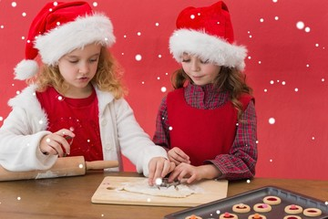 Composite image of festive little girls making christmas cookies