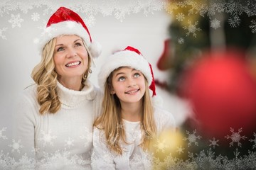 Composite image of festive mother and daughter smiling at tree