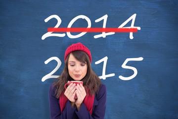 Composite image of festive brunette holding a mug