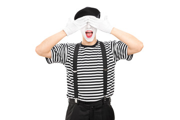 Mime artist covering his eyes