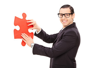 Young businessman holding piece of a puzzle
