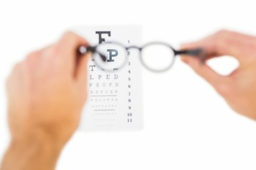 Glasses held up to read eye test