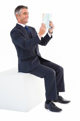 Smiling businessman sitting on a cube reading a book