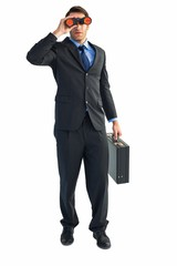 Businessman using binoculars while holding a briefcase