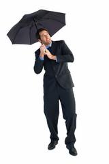 Businessman standing under black umbrella