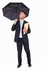 Cheerful businessman holding a file under umbrella