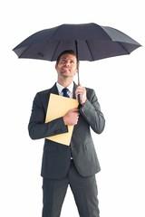 Businessman sheltering under umbrella holding file